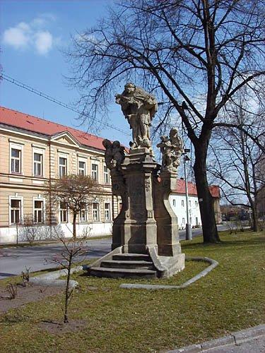 Sousoší Jana Nepomuckého z dílny F.I. Platznera z r. 1755. V pozadí budova obecné školy z r. 1879. foto: RNDr. Aleš Střecha